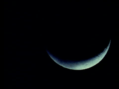 Crescent moon appears in black sky at night from beneath black cloud, moves slowly higher in sky