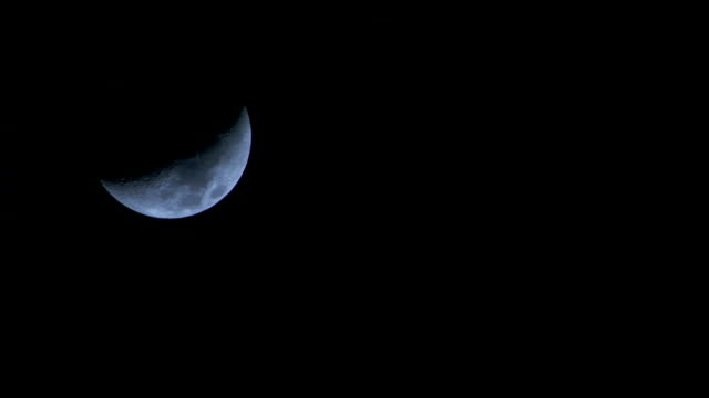 A crescent moon glows in the night sky. Available in HD