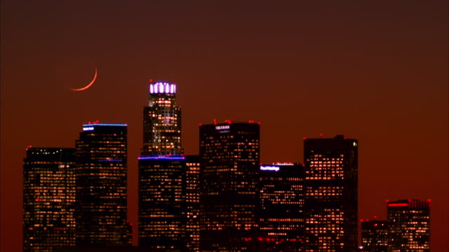 T/L, MS, Crescent moon over silhouettes of skyscrapers against orange sky, Los Angeles, California, USA