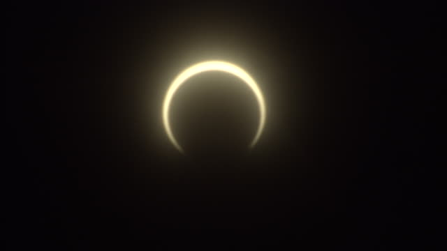 A crescent of sunlight glows around the moon during a solar eclipse.