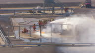 MS AERIAL TS crew hosing down burning pipe at Brayton Fire Training Field / College Station, Texas, United States
