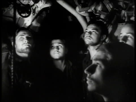 Crew in submarine listening and watching one man putting finger to lips indicating to keep quiet /