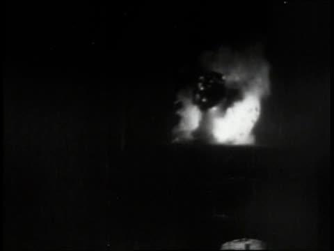 Crew member looking through binoculars watching explosions as target is hit /