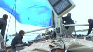 Crew members jibe a giant spinnaker during a yacht race near Newport, Rhode Island.
