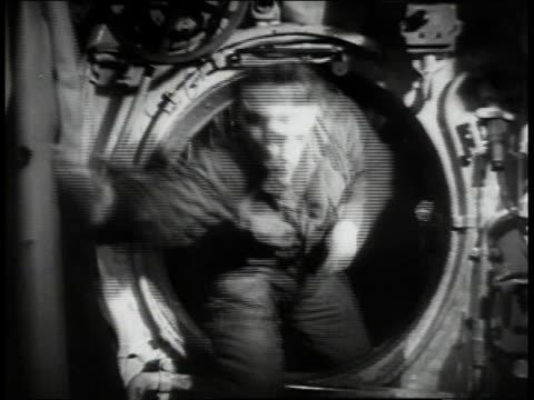 Crew members rushing through submarine man opening hatch /