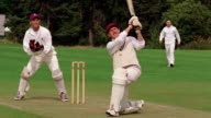 PAN cricket batsman hits ball high + looks up / wicketkeeper + fielder watch/ Hertfordshire, England