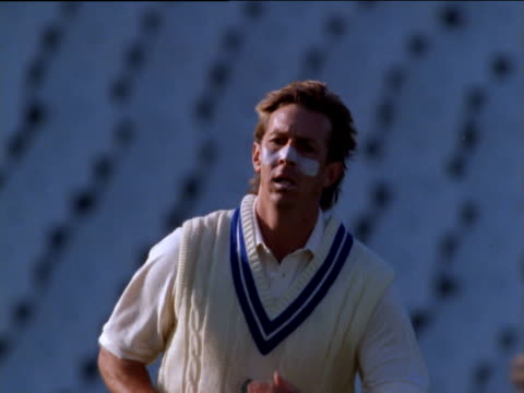 Cricket bowler runs towards camera and bowls, ball hits wicket and toppling bail