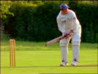 Cricket player in baseball cap batting / England