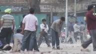 WS Cricket player on street hitting ball / Delhi, Delhi , India