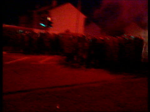 Crime Drumcree march violence NORTHERN IRELAND Portadown Garvaghy Road NIGHT Police in riot gear march along road and scuffles break out as they try...