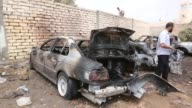 Crime scene investigation team members inspect the burnt vehicles at the site of car bombing attack causing material damage but no casualties near...