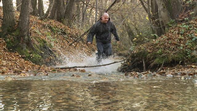 HD SLOW MOTION: Criminal Runner Splashing Through Stream