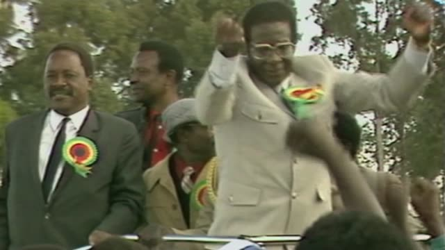 WHO criticised after Mugabe appointment AS010785004 / 171965 Various of Mugabe pumping his fists and waving to crowds as along in vehicle as arriving...