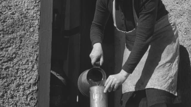 1944 MONTAGE Crofter filling up water container for neighbor / Achriesgill, Scotland, United Kingdom