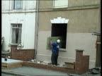 ENGLAND Gloucester Cromwell St MS Window frame as man knocks out bricks LMS Man lifting door out of window frame MS Man carrying door along BV...