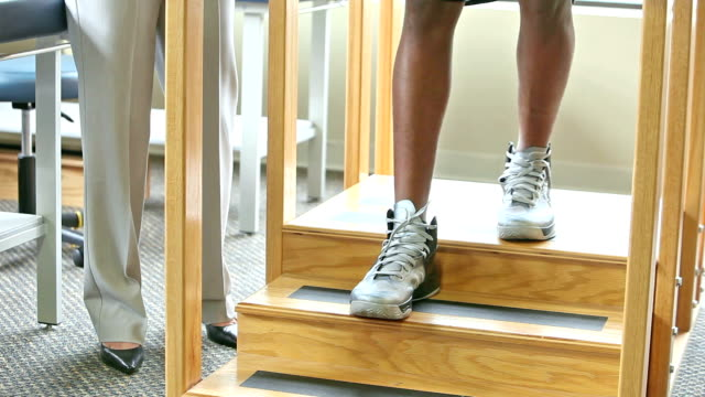 Cropped view, physical therapist with patient on training stairs