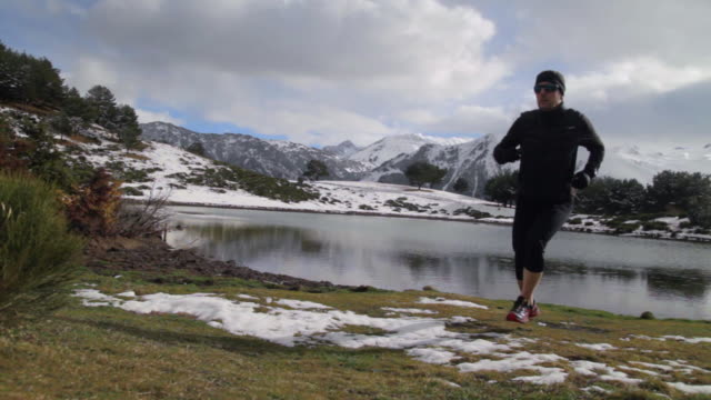 Cross country runner running on the shore of a lake in a snowy mountain range