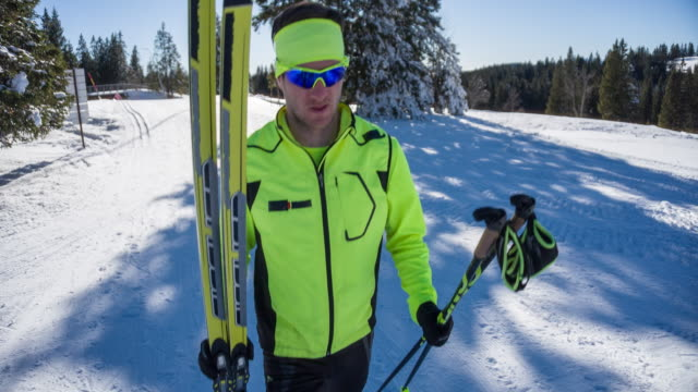 Cross country skier carrying his sports equipment in winter landscape