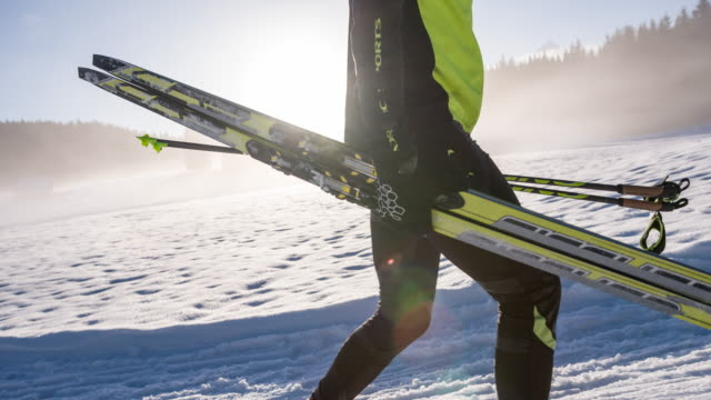 Cross country skier carrying his sports equipment
