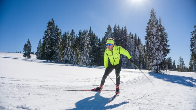 Cross country skier full power skate skiing uphill on a sunny winter day