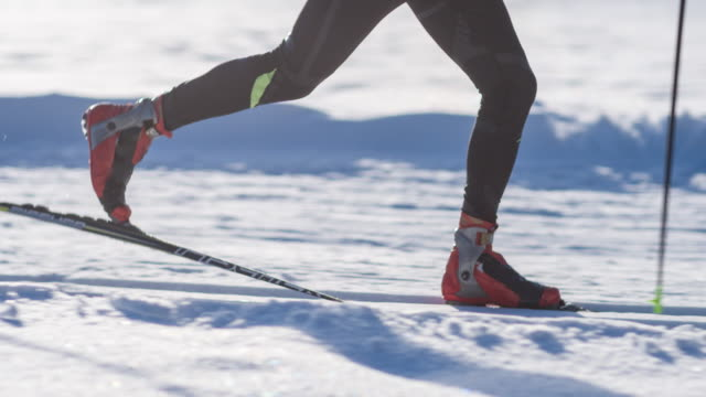 Cross country skier gliding on skiing track in idyllic winter landscape