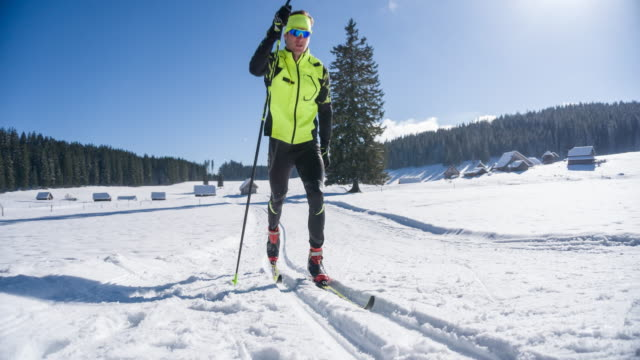 Cross country skier gliding on skiing track in winter landscape
