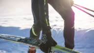 Cross country skier putting his skis on snowy surface