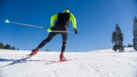 Cross country skier skate skiing uphill on a snowy landscape