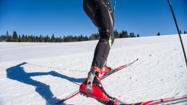 Cross country skier skate skiing uphill on a sunny winter day