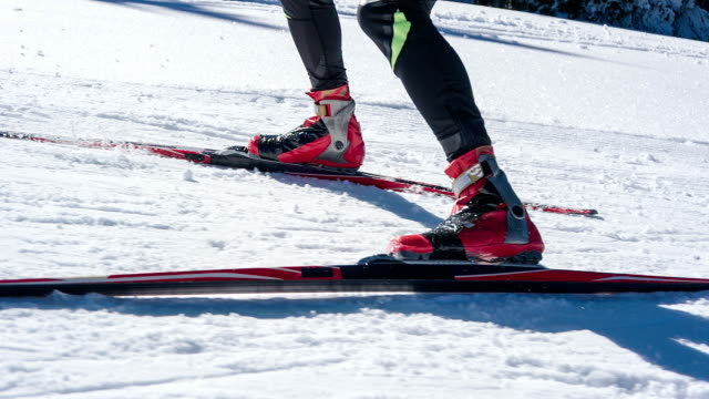 Cross country skiers feet skate skiing uphill
