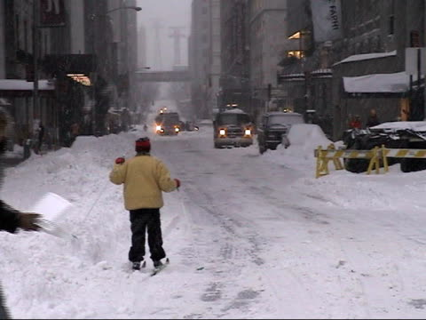 WS, Cross-country skier going down city street in heavy snow, New York City, New York, USA