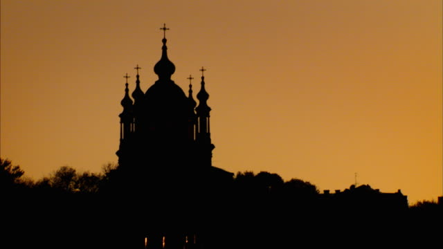 Crosses adorn domes on a silhouetted church. Available in HD.