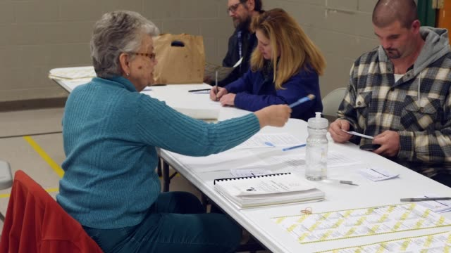 A crosssection of white Michigan voters log in at polling place before they mark their ballots in the 2016 presidential election Michigan voters gave...