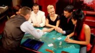Croupier passing cards to blackjack gamblers in casino.