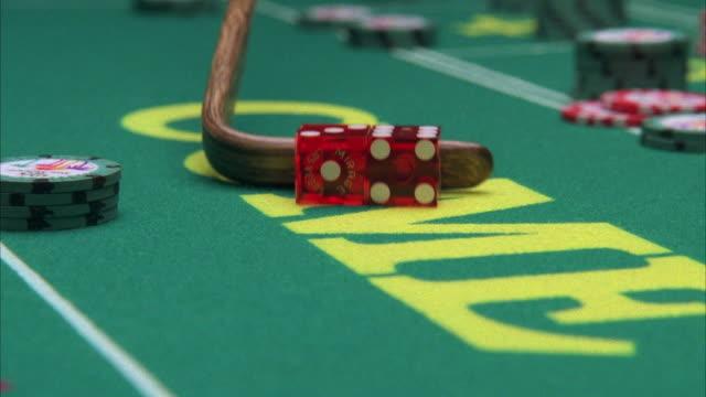 CU R/F Croupier raking dice on craps table in casino / Las Vegas, Nevada, USA