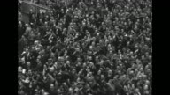 Crowd at Doncaster Racecourse with straightaway / two shots people milling about in infield / Queen Elizabeth waves from her box decorated with...