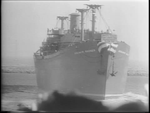 Crowd at Kaiser Shipyard / Mr and Mrs Henry J Kaiser arrive / Liberty ship 'Benjamin Warner' at dock / shipbuilders and Jack and Harry Warner sign...
