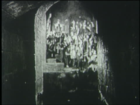 B/W 1925 crowd carrying torches running thru water in sewer