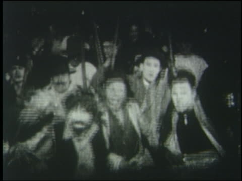 B/W 1925 crowd carrying torches stops running in front of camera at night
