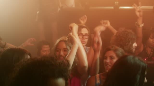 MS TU ZI SLO MO Crowd dancing in nightclub with DJ spinning records / New York City, New York, USA