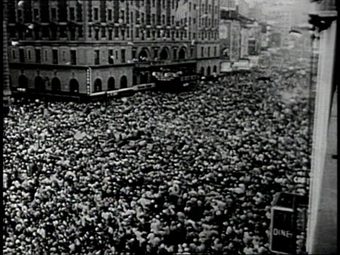 Crowd filling Times Square / People waving newspapers with victory headlines / Soldier kissing a woman / Confetti falling from windows / Sailors and...