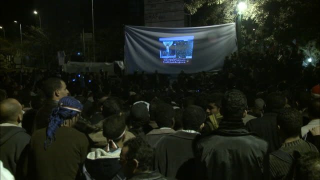 Crowd in Tahrir Square watching video projection of Mubarak's speech on a hanging sheet while cameras are flashing / Cairo Egypt