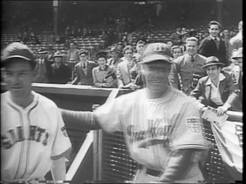 A crowd in the stands of the Polo Grounds of New York City / New York Giants players sitting in the dugout / a group of photographers and cameramen...