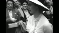 Crowd mills about on grounds beside Ascot Racecourse / Queen Elizabeth II and uncle Prince Henry walk through crowd followed by Princess Margaret /...