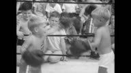 Crowd of children and adults sit and watch two young boy boxers in a miniature wrestling ring / toddler boys keep punching with their boxing gloves /...