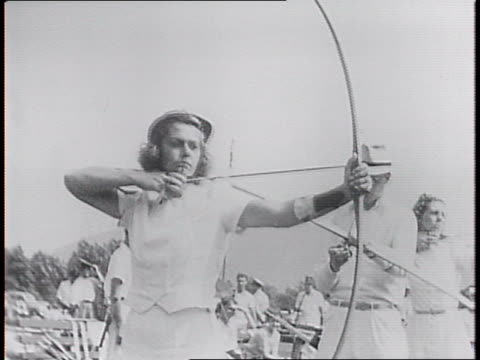 Crowd of competitors and spectators on field / two female competitors aim bows and release arrows at targets / bullseyes on target