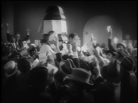 B/W 1929 REENACTMENT crowd of frenzied stockbrokers holding up papers trying to sell /stock exchange