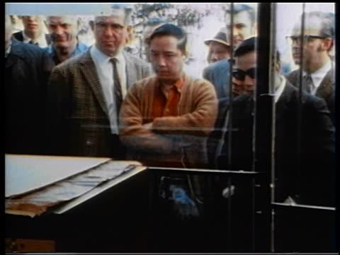 1970 crowd of men intently watching television thru store window