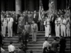Crowd of men standing on steps of city hall including men dressed in white holding American flags being photographed / New York City New York United...