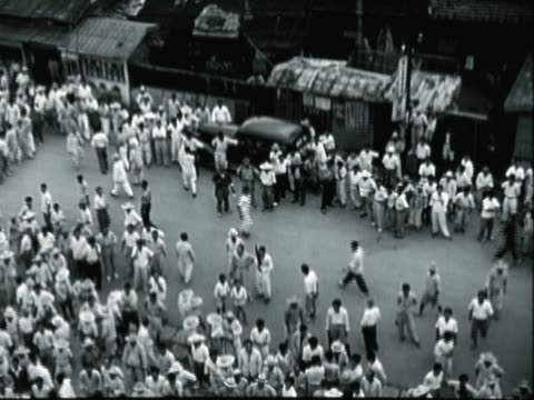 MONTAGE Crowd of North Korean refugees gathering on the street as a United Nation flag waves overhead / North Korea